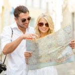 smiling couple with map in the city