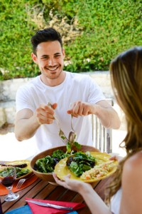 happy young man woman couple having lunch barbecue outdoor in summer with friends